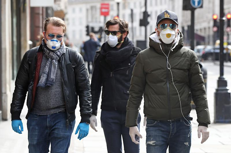 People wearing face masks and gloves in Regents Street in London the day after Prime Minister Boris Johnson called on people to stay away from pubs, clubs and theatres, work from home if possible and avoid all non-essential contacts and travel in order to reduce the impact of the coronavirus pandemic.