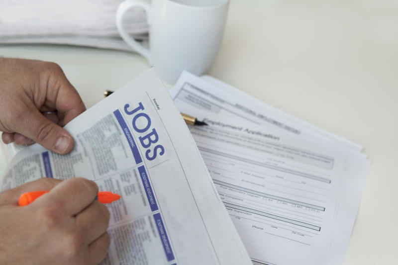 Close-up of hands finding jobs in newspaper with cup in background.