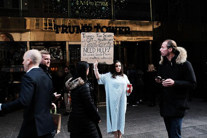 <p>Rosary Solimanto, who has multiple sclerosis and fears for her finances, holds a protest outside of Trump Tower over the Republican administration's proposed tax cut which many economists predict will benefit the wealthy at the expense of the poor and middle class on Nov. 30, 2017 in New York City. (Photo: Spencer Platt/Getty Images) </p>