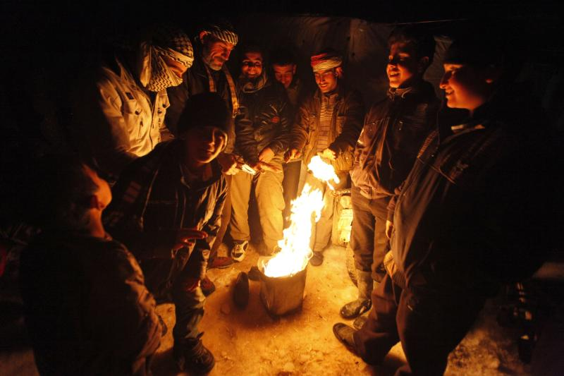 Syrian refugees from the town of Qara gather around a fire to keep themselves warm in a Syrian refugee camp on the Lebanese border town of Arsal, in eastern Bekaa Valley