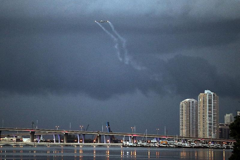 A plane sprays pesticide over Miami on August 12, 2016, in hope of controlling and reducing the number of mosquitos, some of which may be capable of spreading the Zika virus (AFP Photo/Joe Raedle)