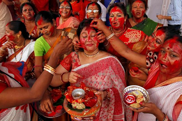 "<p>A woman reacts as ""Sindur"", or vermillion powder, is applied to her face after worshipping an idol of the Hindu goddess Durga on the last day of the Durga Puja festival in Chandigarh, India, Sept. 30, 2017. (Photo: Ajay Verma/Reuters) </p>"