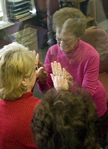 Ruby Klokow, right behind glass, reacts to being sentenced to 10 years in prison Wednesday May 1, 2013, in Sheboygan, Wis., for the 1957 death of her six-month-old daughter. Her sister, Linda Kimpell, tries to hold her hands through the glass. (AP Photo/The Sheboygan Press, Bruce Halmo)