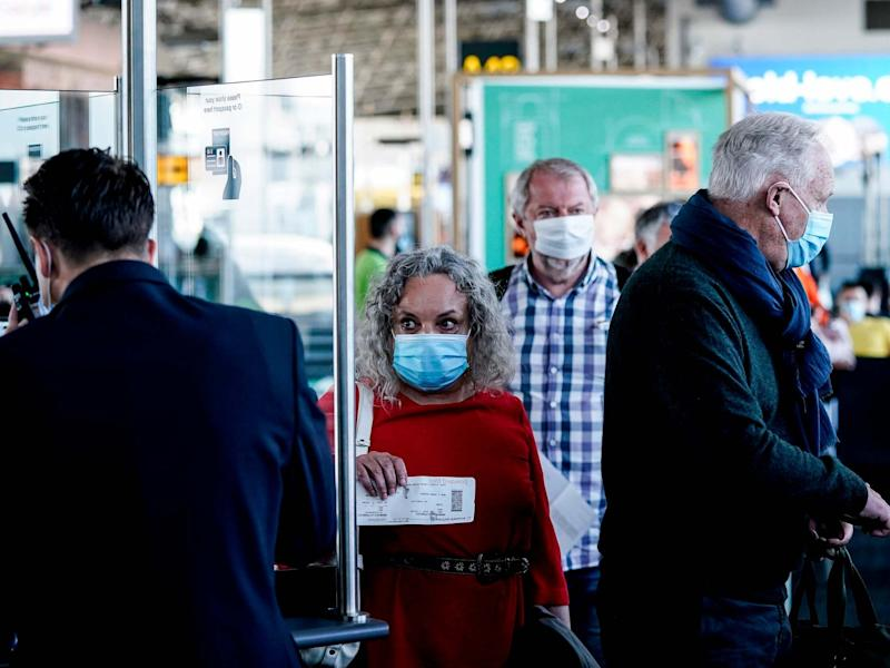 Passengers wearing protective face masks queue at the boarding gate at Brussels Airport, in Zaventem: Kenzo Tribouillard/AFP via Getty Images