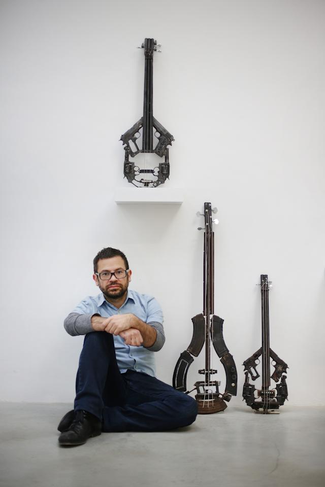 LONDON, ENGLAND - MARCH 26:  Artist Pedro Reyes  sits with some of his musical instruments sculpted from recycled guns at the Lisson Gallery on March 26, 2013 in London, England.  Mexican artist Pedro Reyes received 6,700 destroyed weapons from the Mexican government from which he sculpted two groups of instruments. The first, a series titled Imagine, is an orchestra of fifty instruments, from flutes to string and percussion instruments, designed to be played live. The second, Disarm, is an installation of mechanical musical instruments, which can either be automated or played live by an individual operator using a laptop computer or midi keyboard.  (Photo by Peter Macdiarmid/Getty Images)