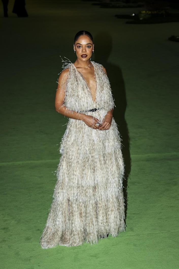 A woman in a feathery white dress posing on a green carpet