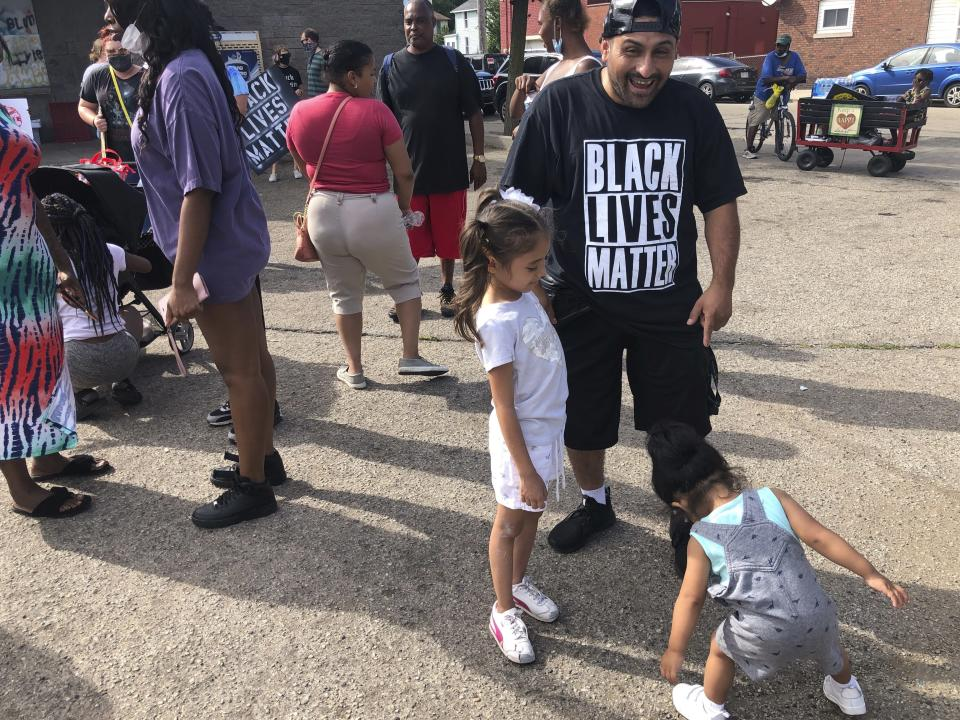 """Angel Crocket, 40, a Kenosha, Wis., resident, and immigrant from Guatemala, dance with his daughters, Yanira, 6, left and Noel, 2, right, on Sunday, Aug. 30, 2020, at an """"Uptown Revival."""" The event was meant to gather donations for Kenosha residents and help businesses hurt by violent protests that sparked fires across the city following the police shooting of Jacob Blake. (AP Photo/ Russell Contreras)"""