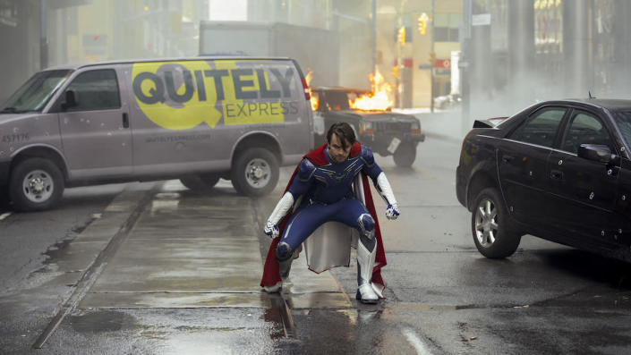 Brandon Sampson dressed in superhero clothes stands in the middle of a rainy street in Jupiter's Legacy.