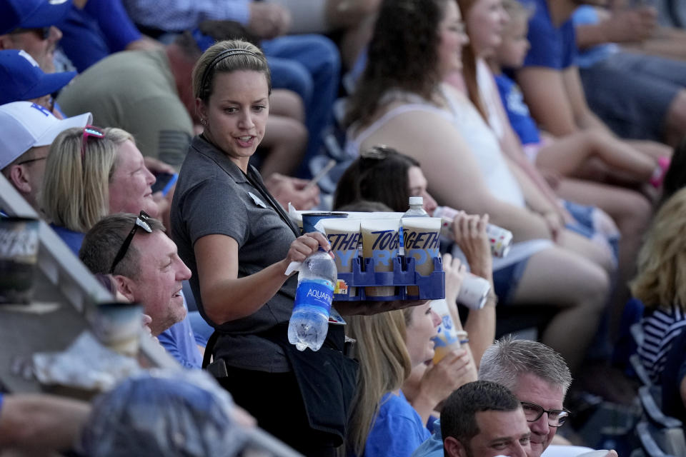 A server delivers drinks to fans during a baseball game between the Kansas City Royals and the Cincinnati Reds Tuesday, July 6, 2021, in Kansas City, Mo. With baseball fans back in the stands and concessions being sold, ballpark employees have had a chance to return after the pandemic hit many of them hard. (AP Photo/Charlie Riedel)