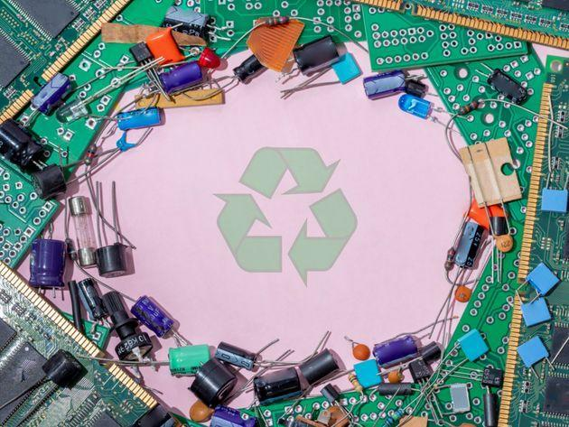 Electronic waste on pink background and green recycling symbol (Photo: Javier Zayas Photography via Getty Images)