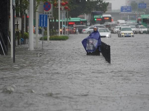 A resident wearing a rain cover stands on a flooded road in Zhengzhou, Henan province, China July 20, 2021. (Photo Credit: REUTERS)