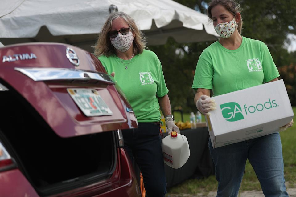 MIAMI, FLORIDA - JULY 24: Karen Sutton (L) and Maggie Izquierdo  place food in the trunk of a vehicle at a drive-thru food distribution site set up at the First Church of the Brethren on July 24, 2020 in Miami, Florida. 500 boxes of food were donated by Farm Share for those in need to help people trying to make ends meet during the pandemic. The United States economic recovery is showing signs of weakness as a renewed outbreak of COVID-19 has caused some business owners to lay employees off again, four months after the initial outbreak of coronavirus in March. (Photo by Joe Raedle/Getty Images)