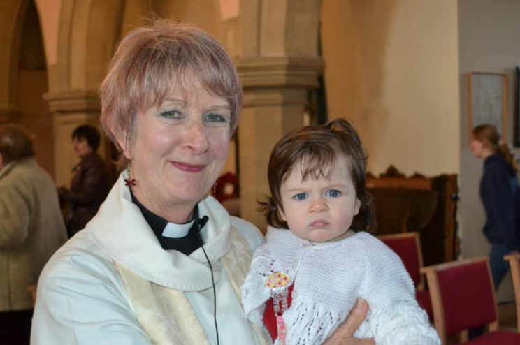 Reverend Wendy Callan poses with her granddaughter Cora, at her baptism. [Photo: Lydia Callan Mosedale]