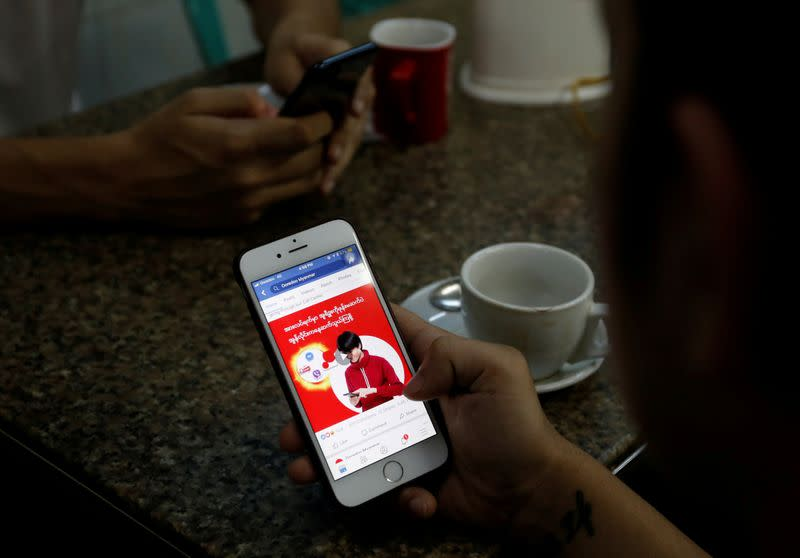 FILE PHOTO: A cellphone user looks at a Facebook page at a shop in Latha street in Yangon