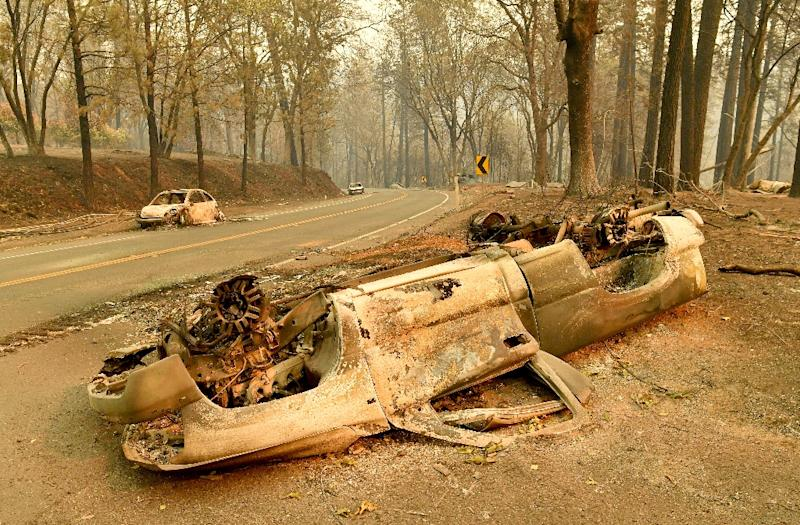 Burned cars litter a road during the Camp fire in Paradise, California on November 12, 2018