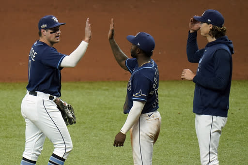 Tampa Bay Rays' Hunter Renfroe, left, celebrates with Randy Arozarena, center, and Tyler Glasnow after the Rays defeated the Toronto Blue Jays during Game 2 of an American League wild-card baseball series Wednesday, Sept. 30, 2020, in St. Petersburg, Fla. (AP Photo/Chris O'Meara)