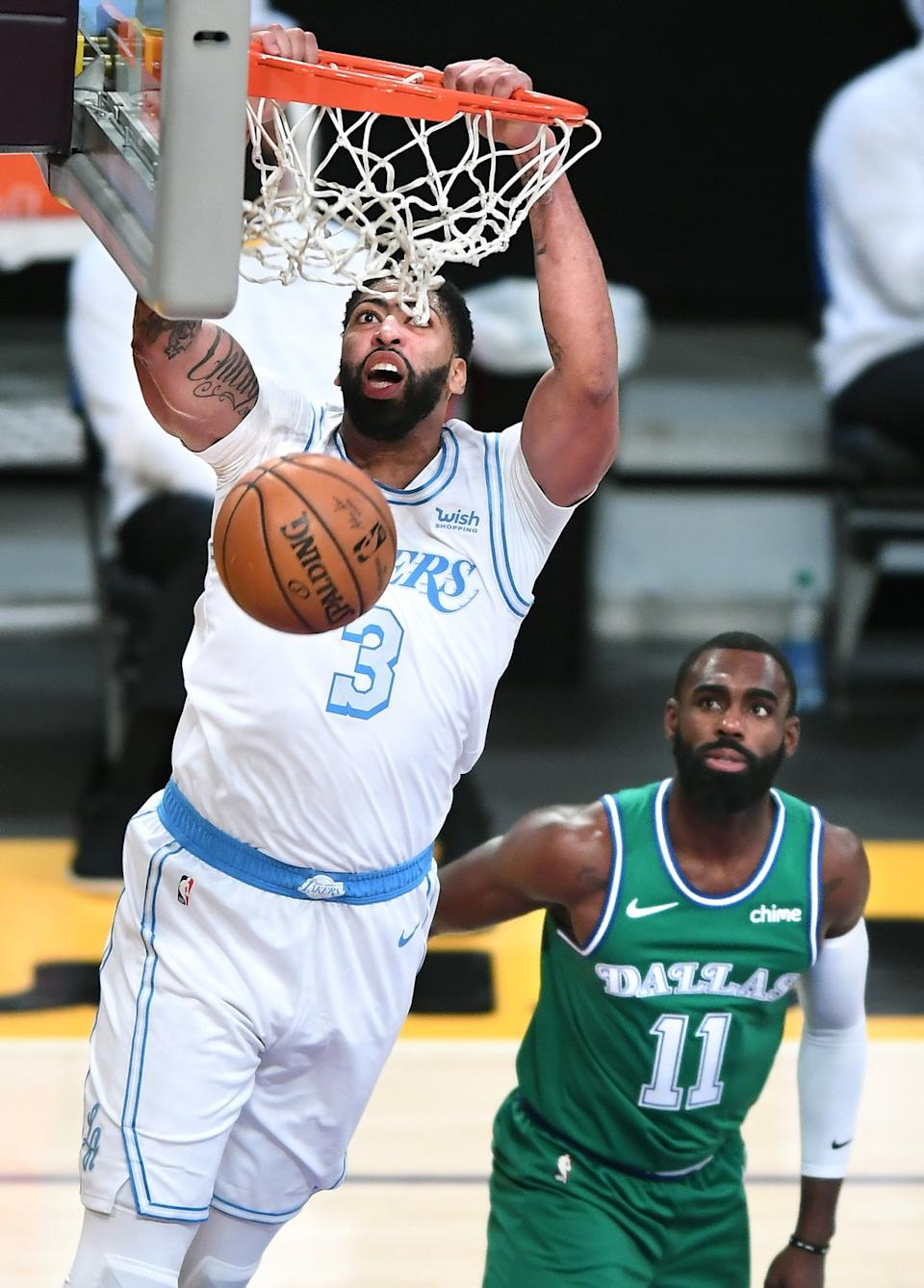 Lakers forward Anthony Davis dunks over Dallas Mavericks guard Tim Hardaway Jr. in the second quarter.