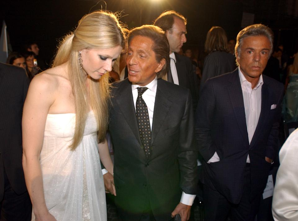 """US actress Gwyneth Paltrow, left, arrives holding hands with Italian designer Valentino, center, as Valentino associate Giancarlo Giammetti, right, looks on, for the """"Una Notte a Roma"""" (a night in Rome) televised fashion show, in Rome's historic Piazza Navona Square, Wednesday, June 1, 2005. The show features collections by Armani, Versace, Valentino and Ferre'. (AP Photo/Corrado Giambalvo)"""