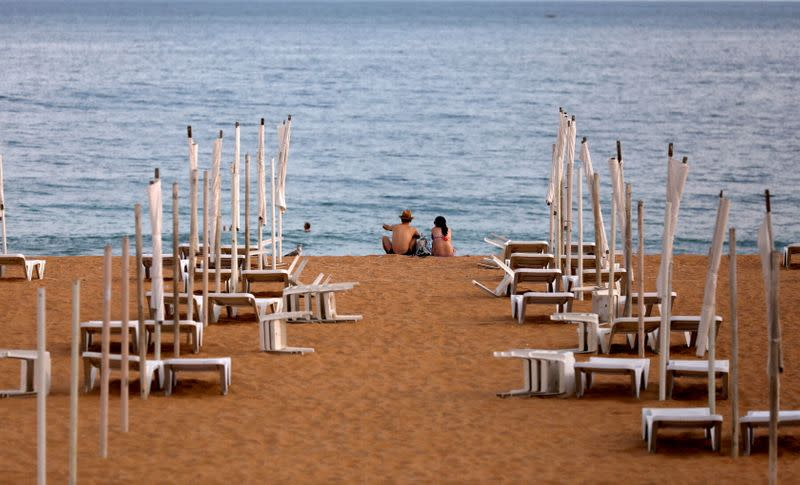 FILE PHOTO: A couple is seen next to rows of empty hammocks during the coronavirus pandemic in Albufeira, Portugal