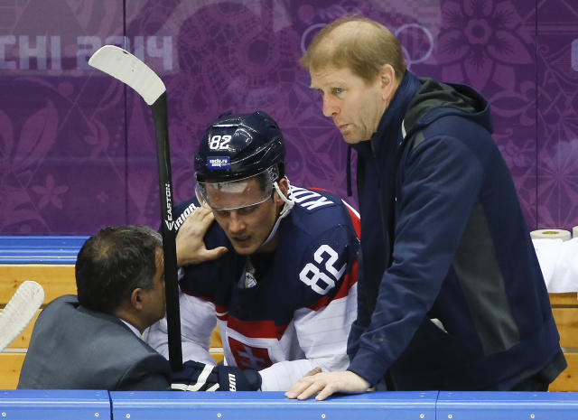 Slovakia forward Tomas Kopecky is checked by a trainer in the first period of a men's ice hockey game against Slovenia at the 2014 Winter Olympics, Saturday, Feb. 15, 2014, in Sochi, Russia. (AP Photo/Mark Humphrey)