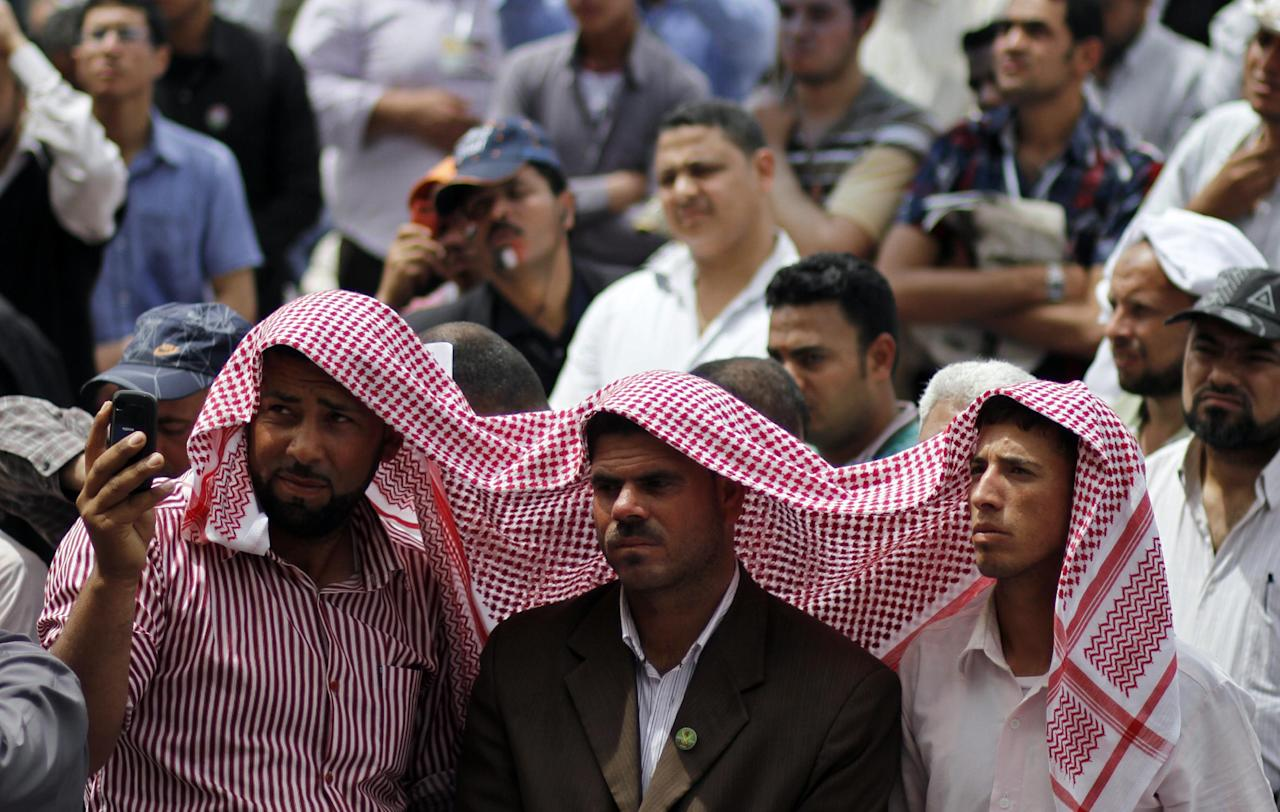 Egyptian protesters use a scarf as a sun shade as they listen to the Friday prayer speech before a rally in Tahrir Square to denounce the presidential candidacies of Hosni Mubarak-era officials, including that of his former spy chief in Cairo, Egypt, Friday, April 13, 2012. Supporters of the country's most influential political group, the Muslim Brotherhood, along with ultraconservative Salafis and other Islamists packed the capital's Tahrir Square, which was the epicenter of the uprising that ousted Mubarak a year ago. (AP Photo/Khalil Hamra)
