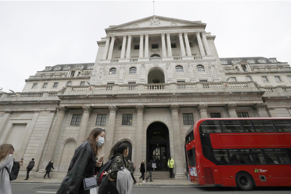 FILE - In this Wednesday, March 11, 2020 file photo, pedestrians wearing face masks pass the Bank of England in London.  The U.K. economy has officially fallen into a recession after official figures showed it contracting by a record 20.4% in the second quarter as a result of lockdown measures put in place to counter the coronavirus pandemic. The slump recorded by the Office for National Statistics follows a 2.2% quarterly contraction in the first three months of the year. ( (AP Photo/Matt Dunham, File)