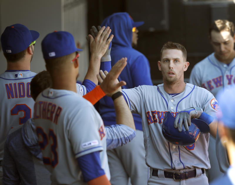 New York Mets' Jeff McNeil, right, celebrates in the dugout after scoring on Robinson Cano's RBI double off Chicago White Sox starting pitcher Dylan Cease, during the sixth inning of a baseball game Thursday, Aug. 1, 2019, in Chicago. (AP Photo/Charles Rex Arbogast)
