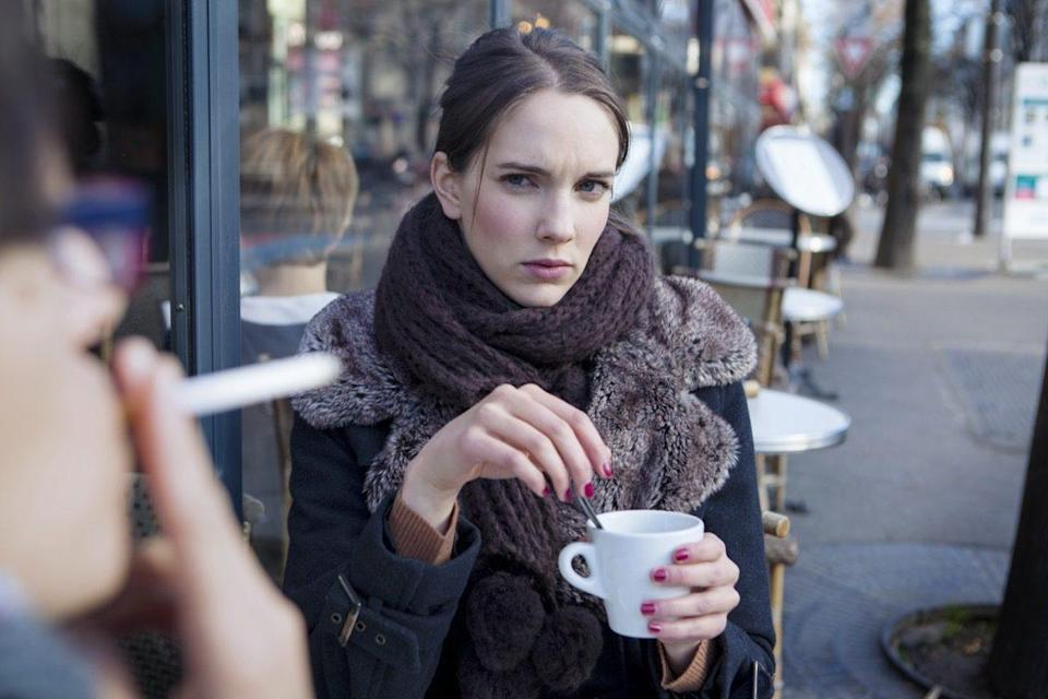 Woman looking displeased at a man smoking outdoor