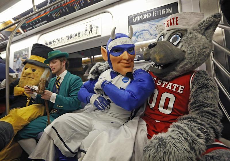 Four of the 15 Atlantic Coast Conference's basketball mascots cram into a New York city subway car for a brief ride, Monday, March 6, 2017, in the Brooklyn borough of New York. All 15 mascots took the ride to promote the ACC basketball tournament March 7-11 at the Barclays Center in Brooklyn. From left, the Wake Forest Demon Deacon, Notre Dame's Leprechaun, Duke's Blue Devil, and North Carolina State's Mr. Wuf. (AP Photo/Kathy Willens)