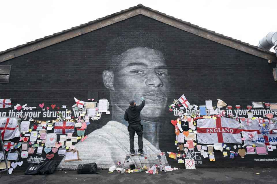 Street artist Akse P19 repairs the mural of Manchester United striker and England player Marcus Rashford on the wall of the Coffee House Cafe on Copson Street, in Withington, Manchester, England, Tuesday July 13, 2021. The mural was defaced with graffiti in the wake of England losing the Euro 2020 soccer championship final match to Italy, but subsequently covered with messages of support by well wishers. (AP Photo/Jon Super, File)