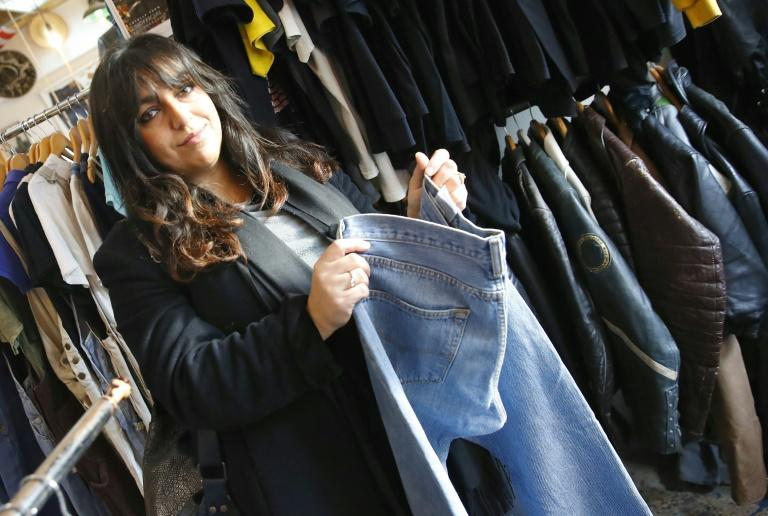 Batia Leora Deil, part of a group known as Anusim -- Jews who have inwardly renounced strict haredi practices -- checks clothes at a store in Israel's Mediterranean city of Tel Aviv (AFP Photo/JACK GUEZ)