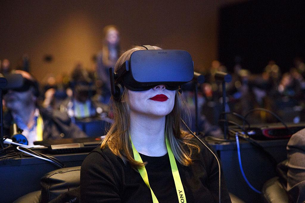An attendee wears an Oculus Rift virtual reality (VR) headset during the Intel Corp. press event at the 2017 Consumer Electronics Show (CES) in Las Vegas, Nevada, U.S., on Wednesday, Jan. 4, 2017. Intel, trying to convert its dominance of computers into a stake in the growing market for chips used in cars, is offering automakers new products aimed at making its technology crucial to the effort to develop self-driving vehicles. Photographer: Patrick T. Fallon/Bloomberg via Getty Images