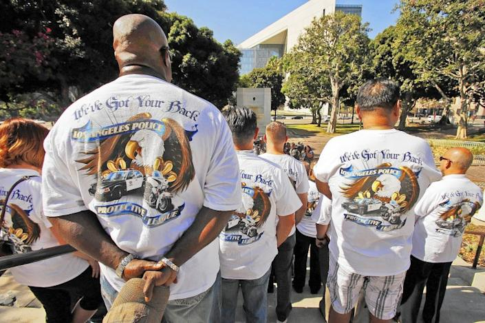 Officer Dwayne Wilson, left, joins LAPD members wearing shirts in support of the Los Angeles Police Protective League during a press conference at City Hall.