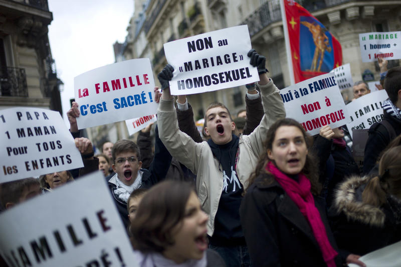 "Young people hold placards during a protest organized by fundamentalist Christian group Civitas Institute against the gay marriage, in Paris, Sunday, Nov. 18, 2012. Placards at center read: ""No to Homosexual Marriage"", and at left: ""Family is Sacred"". (AP Photo/Thibault Camus)"