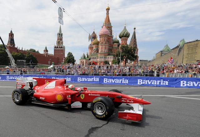 """Formula One Scuderia Ferrari team pilot Giancarlo Fisichella drives past St. Basils cathedral during the """"Moscow City Racing"""" show on July 17, 2011 in central Moscow. AFP PHOTO / NATALIA KOLESNIKOVA (Photo credit should read NATALIA KOLESNIKOVA/AFP/Getty Images)"""