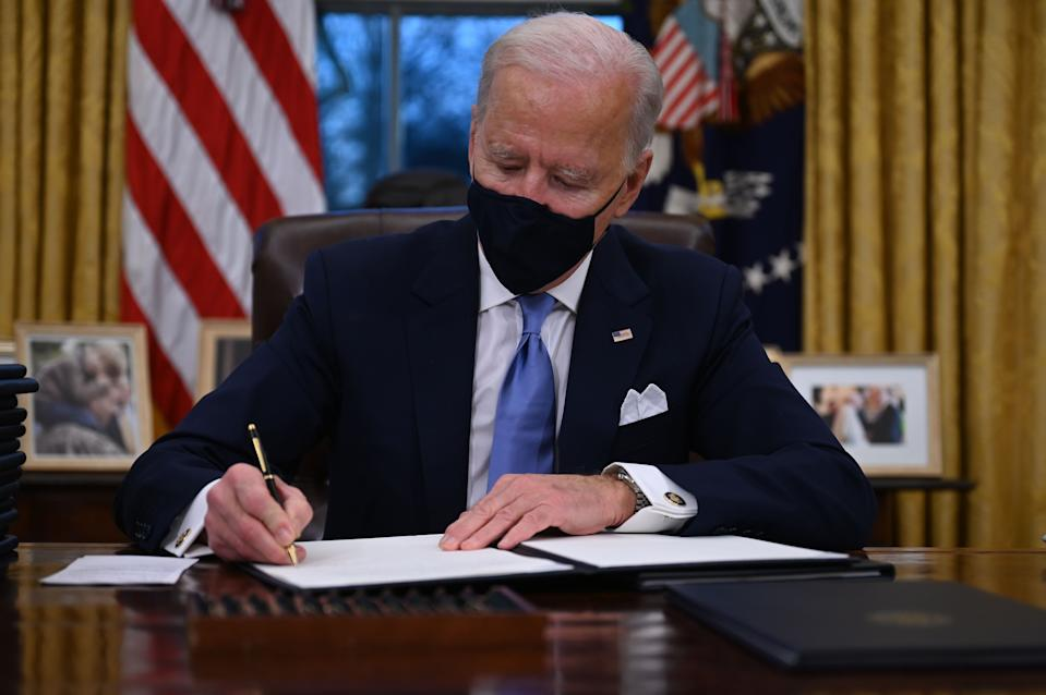US President Joe Biden sits in the Oval Office as he signs a series of orders at the White House in Washington, DC, after being sworn in at the US Capitol on January 20, 2021. - US President Joe Biden signed a raft of executive orders to launch his administration, including a decision to rejoin the Paris climate accord. The orders were aimed at reversing decisions by his predecessor, reversing the process of leaving the World Health Organization, ending the ban on entries from mostly Muslim-majority countries, bolstering environmental protections and strengthening the fight against Covid-19. (Photo by Jim WATSON / AFP) (Photo by JIM WATSON/AFP via Getty Images)