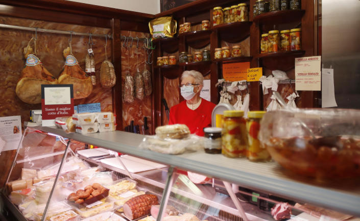 In this photo taken on Thursday, March 12, 2020, a shopkeeper wears a mask as she stands in her deli meat and cold cuts shop in Codogno, Italy. The northern Italian town that recorded Italy's first coronavirus infection has offered a virtuous example to fellow Italians, now facing an unprecedented nationwide lockdown, that by staying home, trends can reverse. Infections of the new virus have not stopped in Codogno, which still has registered the most of any of the 10 Lombardy towns Italy's original red zone, but they have slowed. For most people, the new coronavirus causes only mild or moderate symptoms. For some it can cause more severe illness. (AP Photo/Antonio Calanni)