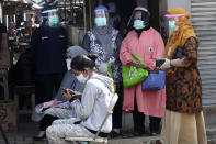 Health Ministry officials wearing protective gears, standing, look on as people wait to have their nasal swab samples collected during a mass test for the new coronavirus at a market in Jakarta, Indonesia, Thursday, June 25, 2020. (AP Photo/Tatan Syuflana)