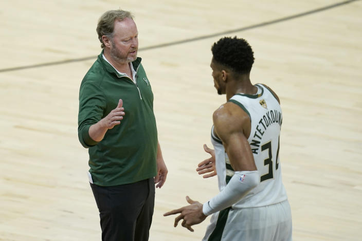 Milwaukee Bucks head coach Mike Budenholzer, left, greets forward Giannis Antetokounmpo during the second half of Game 2 of basketball's NBA Finals against the Phoenix Suns, Thursday, July 8, 2021, in Phoenix. (AP Photo/Ross D. Franklin)