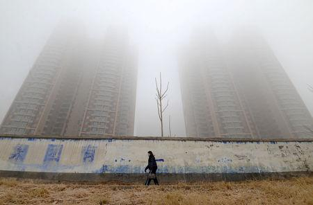 FILE PHOTO - Woman wearing a mask walks past buildings on a polluted day in Hebei