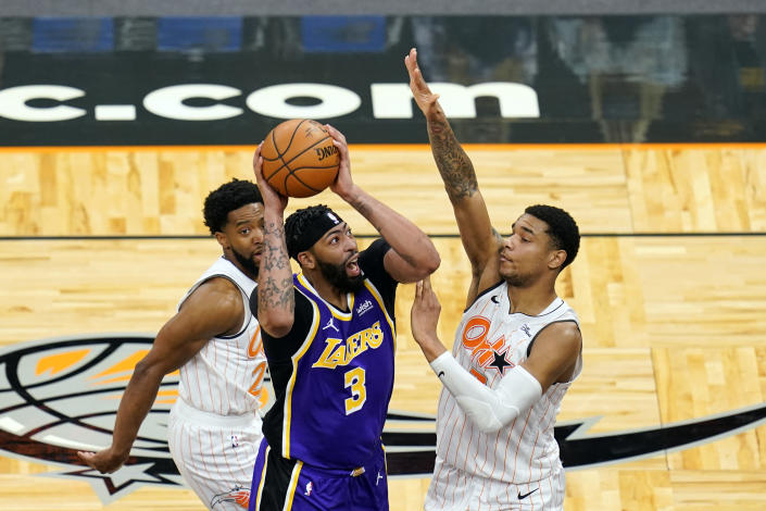 Los Angeles Lakers forward Anthony Davis (3) takes shot as he gets between Orlando Magic guard Chasson Randle, left, and forward Chuma Okeke (3)during the first half of an NBA basketball game, Monday, April 26, 2021, in Orlando, Fla. (AP Photo/John Raoux)
