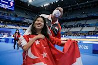Singapore's Yip Pin Xiu celebrates with a national flag after winning women's 100m backstroke gold