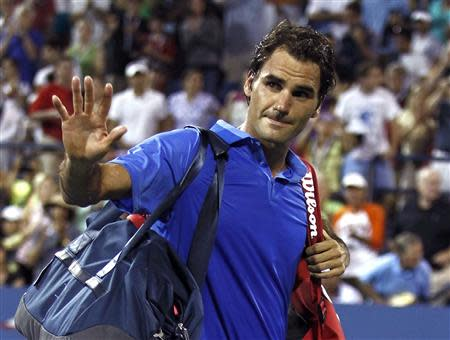 Roger Federer of Switzerland waves as he walks off the court after losing in three sets to Tommy Robredo of Spain at the U.S. Open tennis championships in New York September 2, 2013. REUTERS/Eduardo Munoz