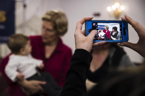 Warren holds a baby during a selfie line in Philadelphia. She had promised to take photos early on in her speech: