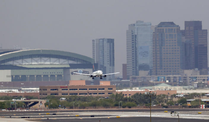 Heat waves ripple across the tarmac at Sky Harbor International Airport as downtown Phoenix stands in the background as an airplane lands, Tuesday, June 20, 2017 in Phoenix. The Phoenix City Council is mulling a vote to raise fees charged ride-hailing companies to $4 per trip to and from the airport. Council members Wednesday, Dec. 18, 2019 are to decide on the proposal to increase the current fee from $2.66 per pickup. (AP Photo/Matt York)