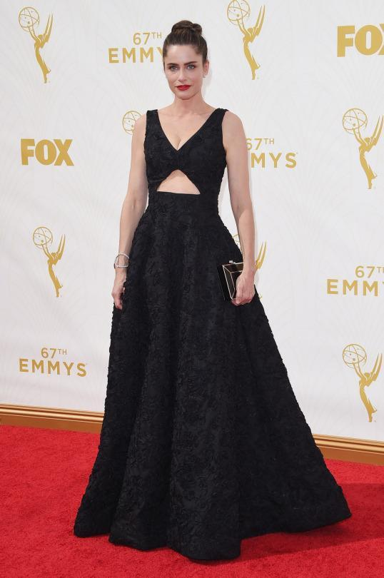 """<p>With a red lip and high bun, Amanda Peet, whose husband is one of the men behind """"Game of Thrones,"""" let her beauty do the talking. She wore a Michael Kors black gown with a stomach cutout that, while beautiful, let everything else stand out.<br></p>"""