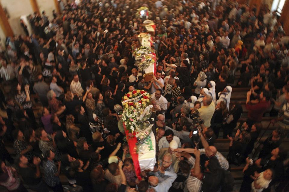 File - In this Tuesday Nov. 2, 2010 file photo, mourners carry the coffins of slain Christians during their funeral in Baghdad, Iraq, who were killed Sunday when gunmen stormed a church during mass and took the entire congregation hostage. The attack, claimed by an al-Qaida-linked organization, was the deadliest recorded against Iraq's Christians since the 2003 U.S.-led invasion unleashed a wave of violence against them. (AP Photo/Khalid Mohammed, File)
