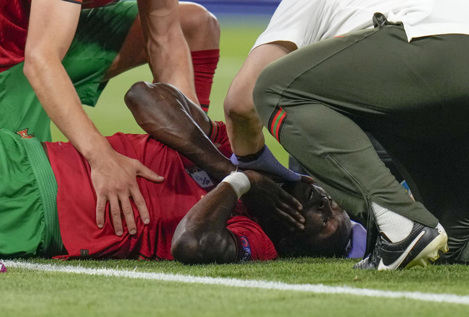 Portugal's Danilo Pereira receives treatment following collision with France's goalkeeper Hugo Lloris during the Euro 2020 soccer championship group F match between Portugal and France at the Puskas Arena, Budapest, Hungary, Wednesday, June 23, 2021. (AP Photo/Darko Bandic,Pool)
