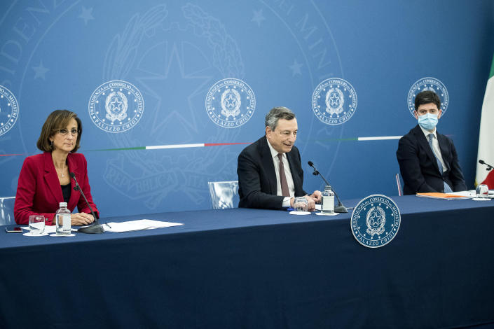 """Italian Premier Mario Draghi, center, sits beside Justice Minister Marta Cartabia, left, and Health Minister Roberto Speranza during a press conference at Chigi Palace government office in Rome, Thursday, July 22, 2021. With COVID-19 cases rising again, Italy will start requiring people to have a so-called """"green pass"""" to access venues like gyms, museums and indoor restaurants. Certification that one is vaccinated, has recovered from COVID-19 in the last six months or tested negative in the previous 48 hours will let people dine at indoor restaurants, go to movies, sports events, casinos and other indoor recreational venues. (Roberto Monaldo/LaPresse via AP)"""