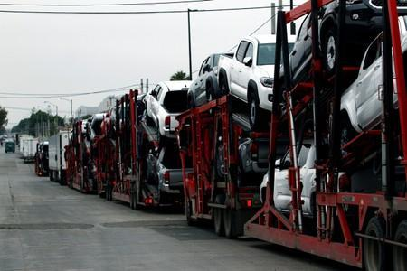 A carrier trailer transports Toyota cars for delivery while queuing at the border customs control to cross into the U.S.
